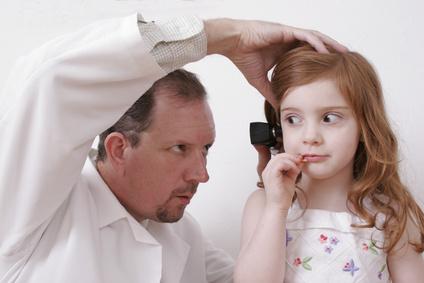 Kinderarzt untersucht die Ohren eines Mädchens