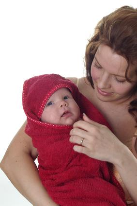 Baby nach der Pflege in Handtuch