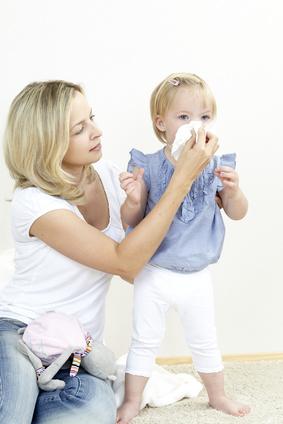 Mutter laesst Kind in ein Taschentuch schnaeutzen