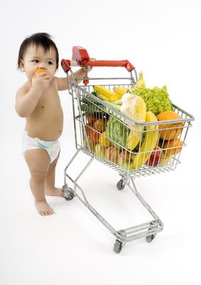Baby schiebt einen Einkaufswagen mit gesunder Ernährung vor sich her