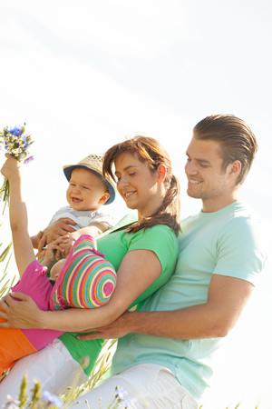 Familie gluecklich mit Baby im Urlaub