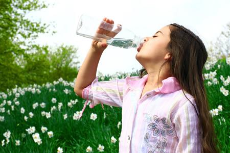 Maedchen loescht seinen Durst mit Wasser