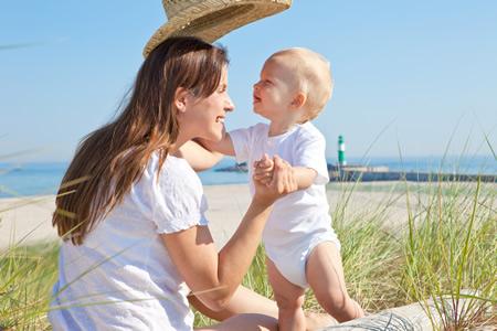 Mutter mit Baby auf Reisen am Strand
