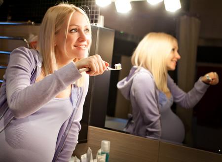 Schwangere putzt sich die Zaehne und achtet auf die Veraenderung ihres Hormonhaushalts SSW 22-23