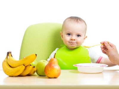 Ein Baby sitzt am Tisch mit Obst
